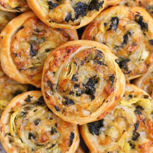 overhead closeup view of a pile of spinach and artichoke puff pastry swirls