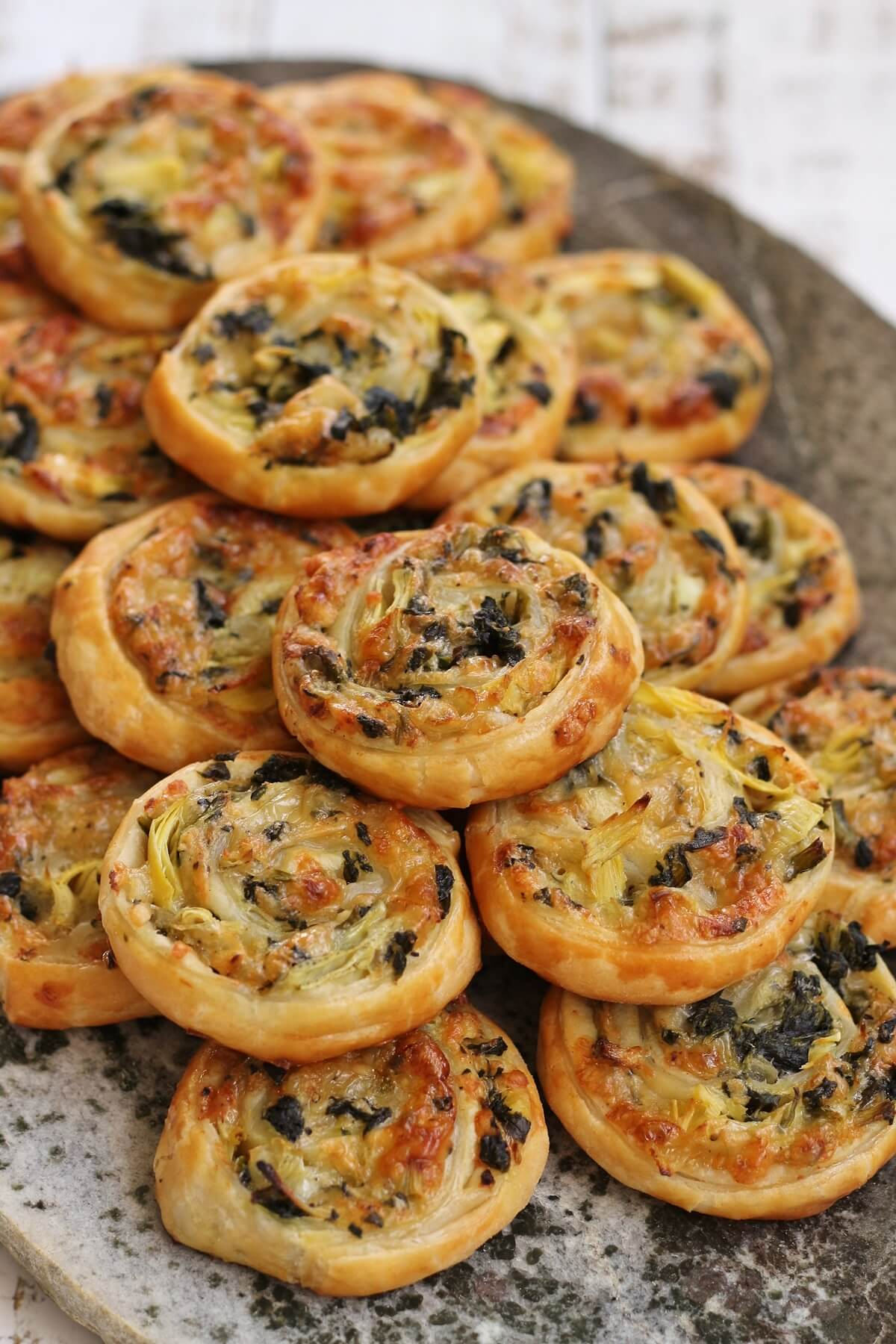 a pile of crispy spinach and artichoke puff pastry swirls on a stone surface