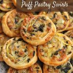 golden brown spinach and artichoke puff pastry swirls piled high on a platter