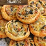 a closeup of flaky spinach and artichoke puff pastry pinwheels on a stone surface