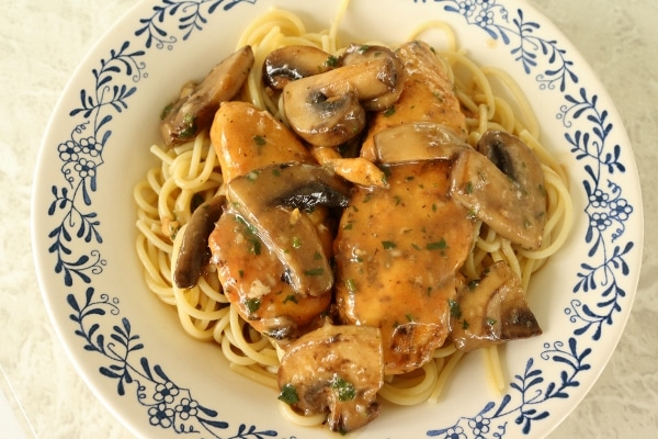 chicken marsala with mushrooms over spaghetti in a wide white bowl with blue decorations