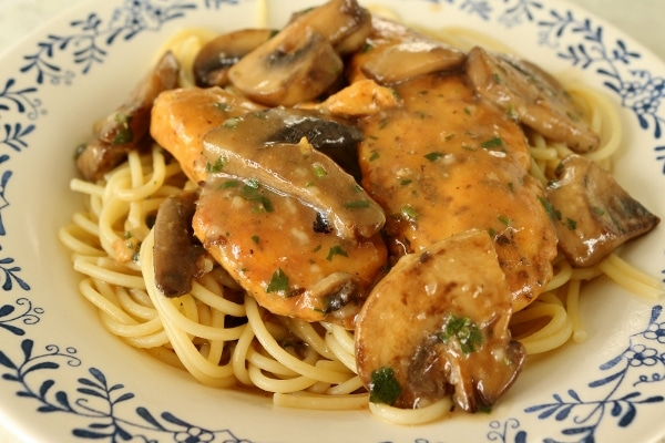 chicken marsala on top of spaghetti in a shallow white bowl with blue decorations