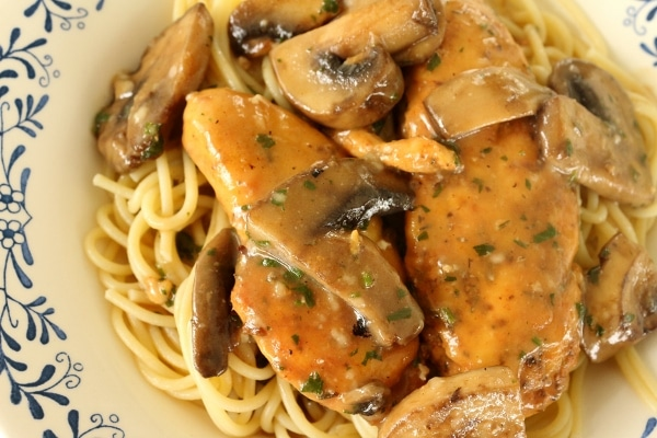 overhead closeup of chicken marsala made with thicken tenders and mushrooms over spaghetti