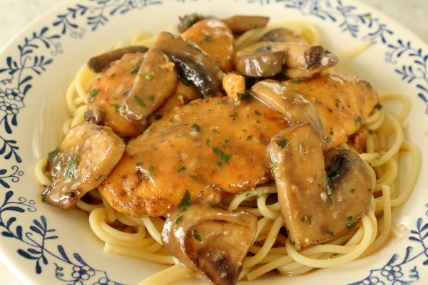 a closeup of chicken marsala made with chicken tenders and mushrooms served over spaghetti