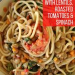 Spaghetti with lentils, roasted tomatoes, and spinach in a wide bowl