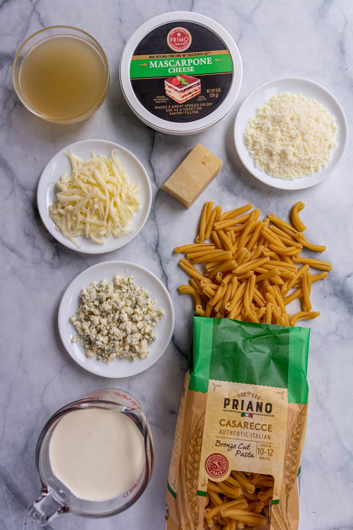 Dry pasta, cream, chicken broth, and five types of cheese on a white marble background.