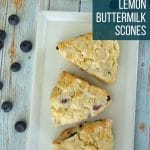 3 blueberry lemon scones on a rectangular white plate with spilled blueberries on the table