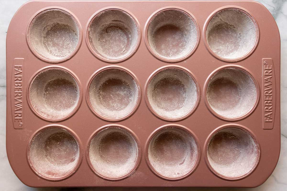 A pink muffin pan with the cups dusted with flour.