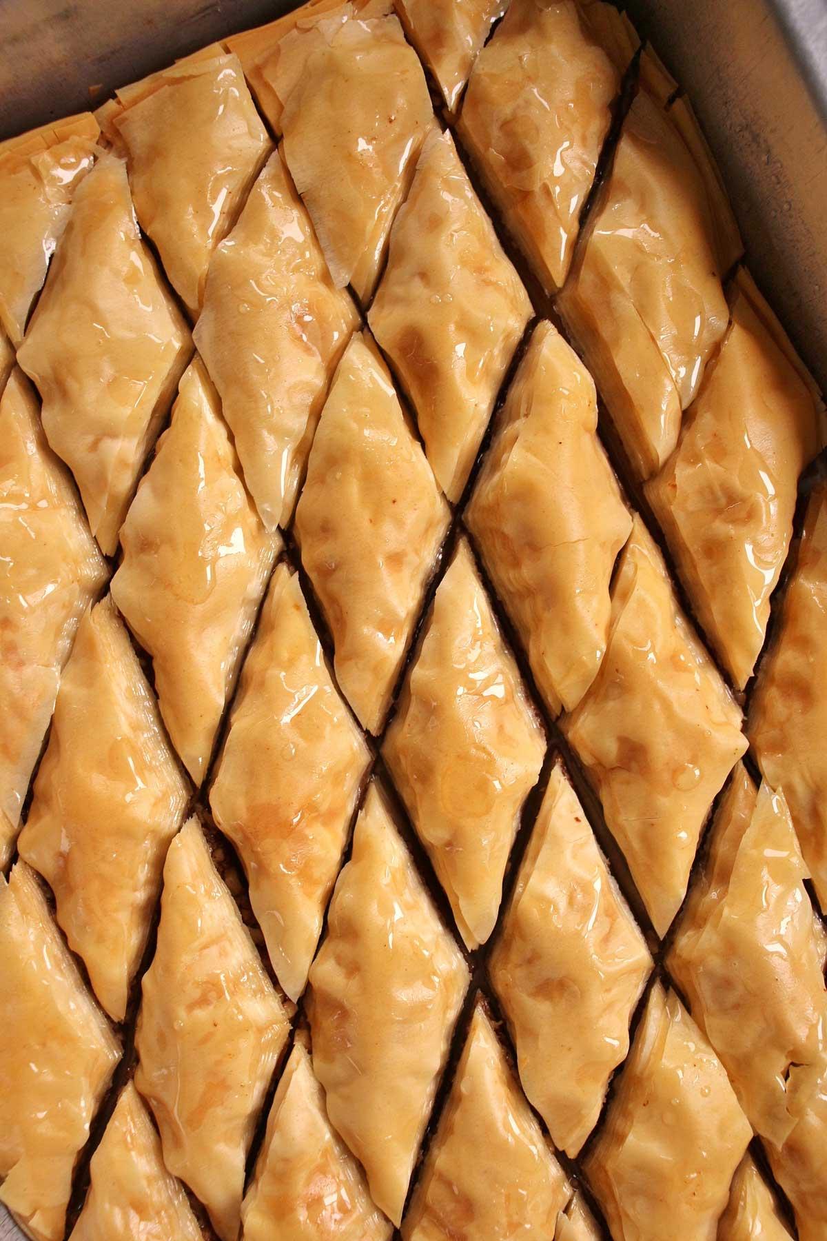 Closeup of a tray of diamond-shaped Armenian baklava soaking with syrup.