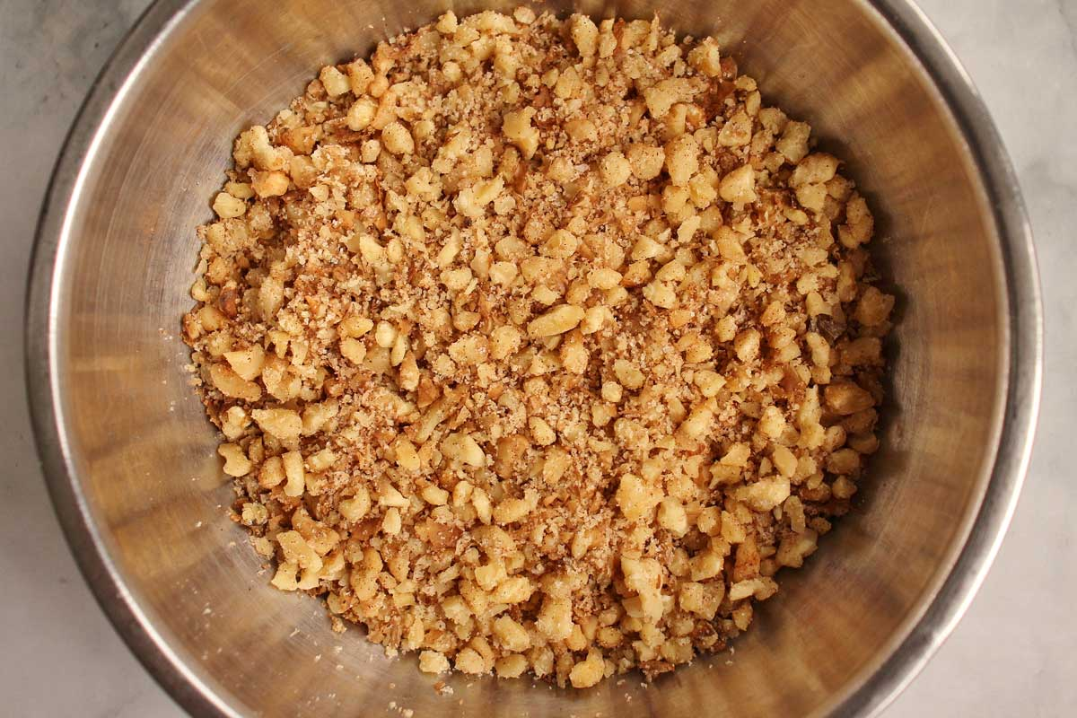Chopped walnuts with cinnamon and sugar in a metal mixing bowl.