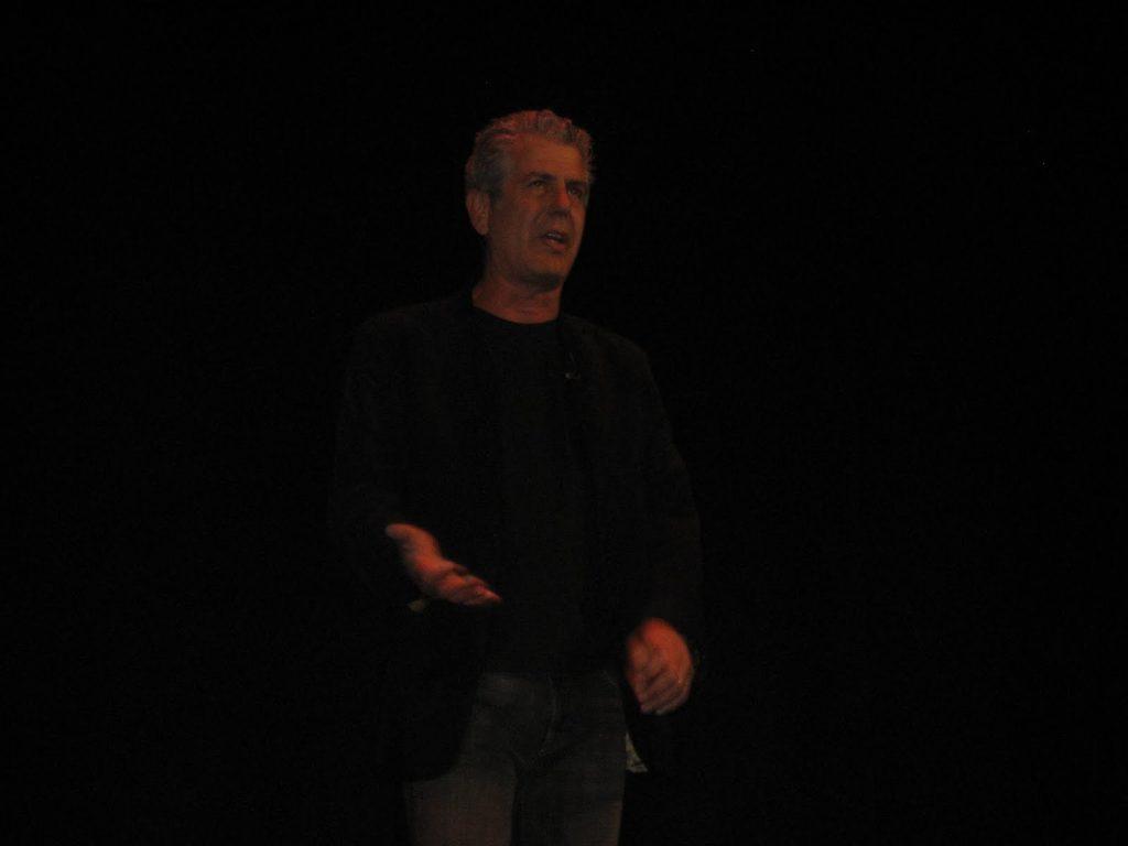 Anthony Bourdain standing in a dark room