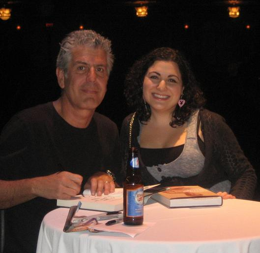 Anthony Bourdain posing with a female fan behind a table