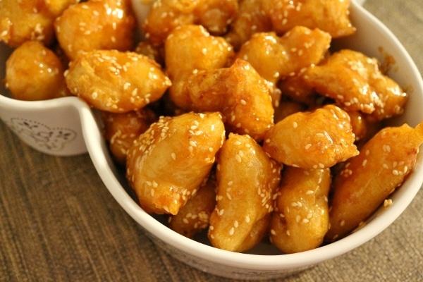 fried honey sesame chicken pieces in a white casserole dish