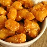 battered fried pieces of chicken in honey sauce with sesame seeds