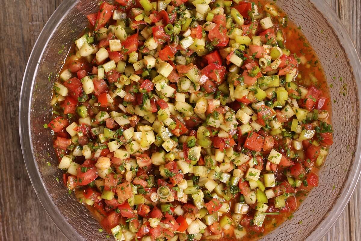 a big mixing bowl of chopped salad with tomatoes, cucumbers, and peppers