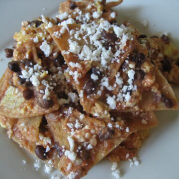 a plate of chilaquiles tortilla chips in red sauce with black beans and cheese