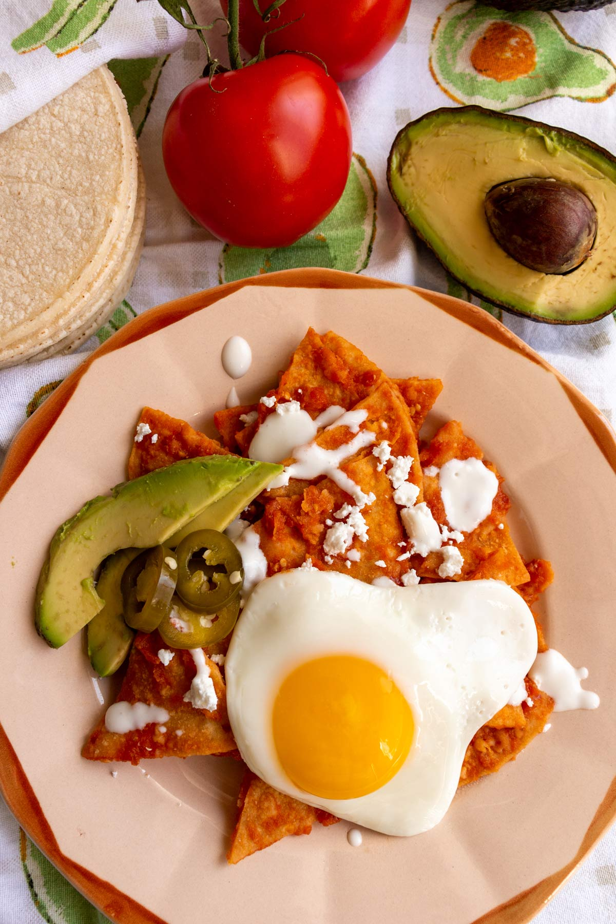 A plate of chilaquiles with corn tortillas, tomatoes, and avocado next to it.