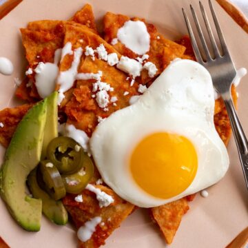 Closeup of a retro plate of red chilaquiles with avocado and fried egg on top.
