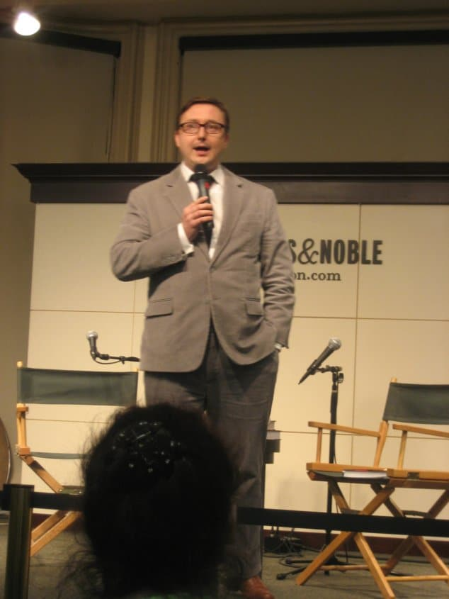 John Hodgman wearing a suit and tie standing in a room