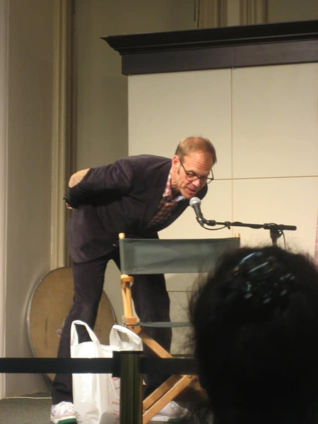 Alton Brown leaning down to speak into a microphone