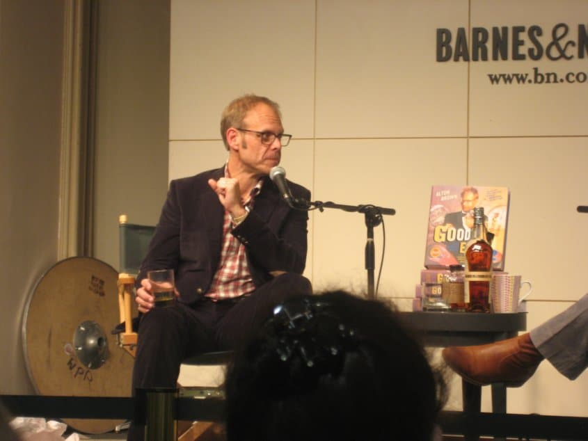 Alton Brown sitting in a chair and talking into a microphone