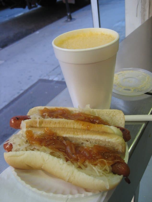 A close up of two hot dogs and a drink on a table