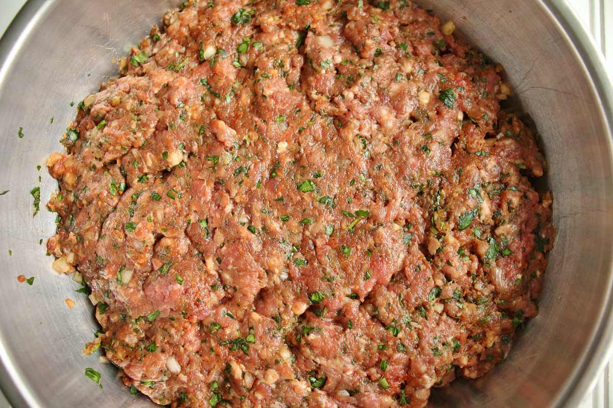 A mixture of ground beef, chopped onions, parsley, and spices in a metal bowl.