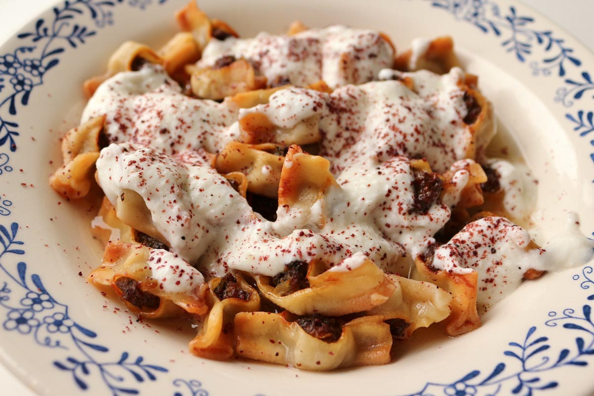 Armenian manti dumplings in a wide white bowl topped with yogurt sauce.