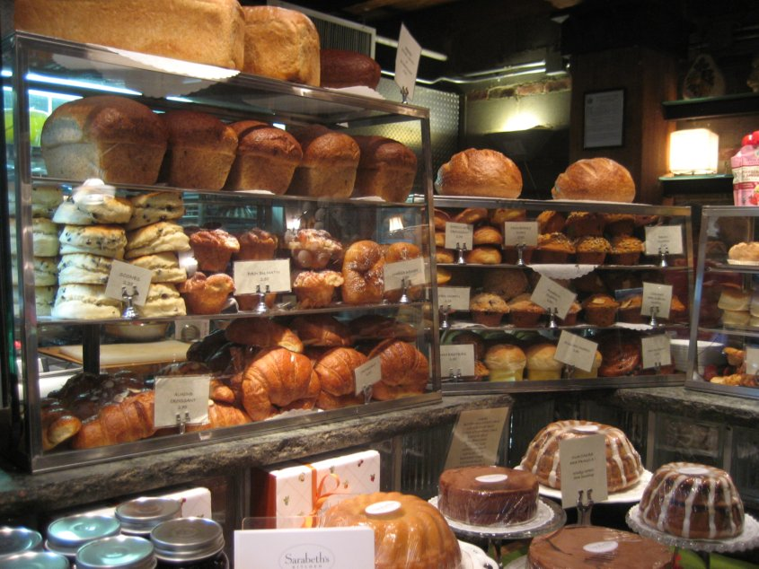 A display in a bakery with lots of breads and other baked goods for sale