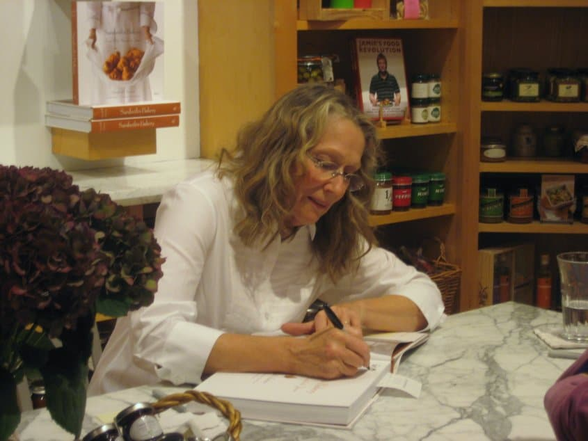 A woman sitting at a table signing a book