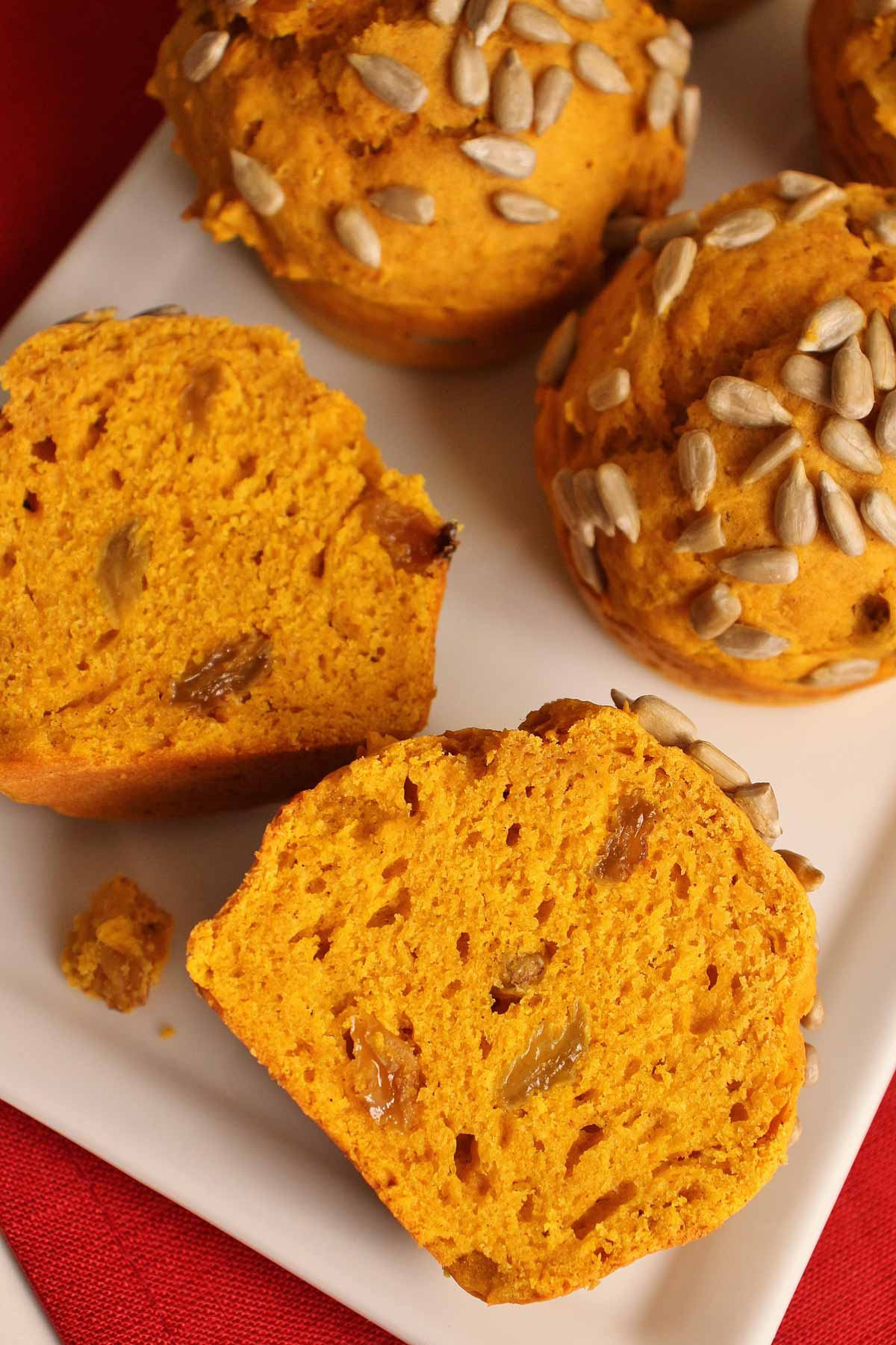 Pumpkin muffins on a white plate with one cut in half to show golden raisins inside.