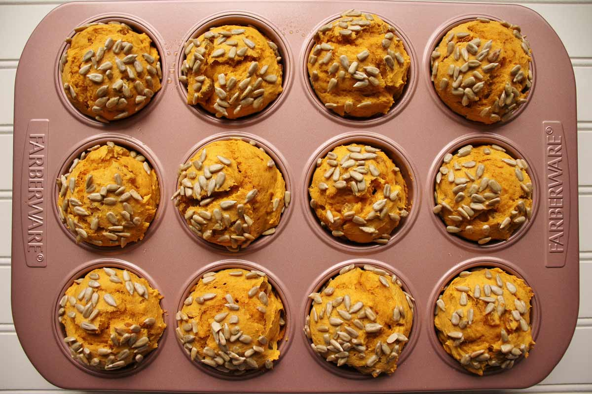 A pink muffin pan filled with bright orange muffins topped with sunflower seeds.