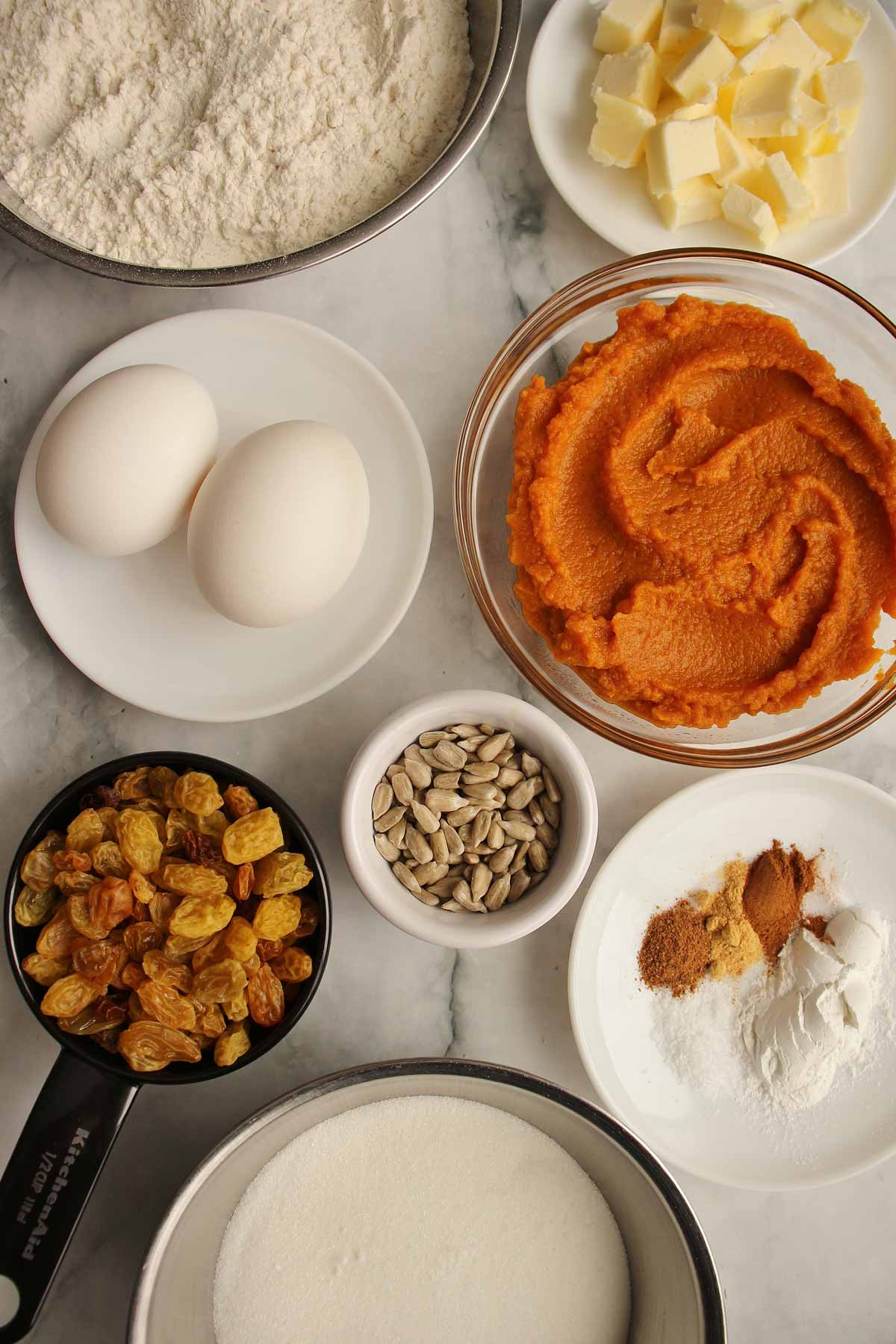 Ingredients for pumpkin raisin muffins including eggs, butter, pumpkin puree, sugar, flour, and spices.