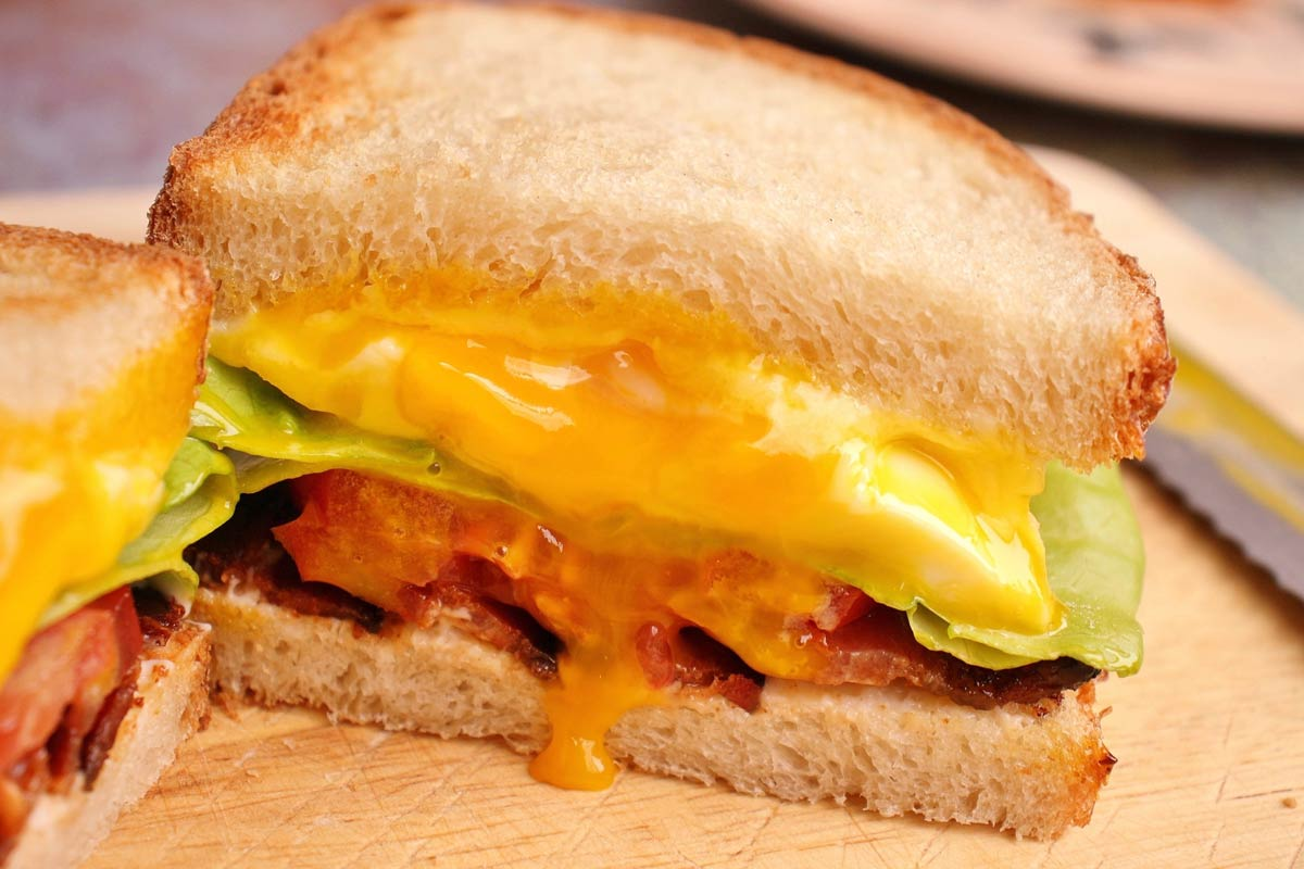 Closeup of a halved sandwich with runny egg yolk on a wooden board.