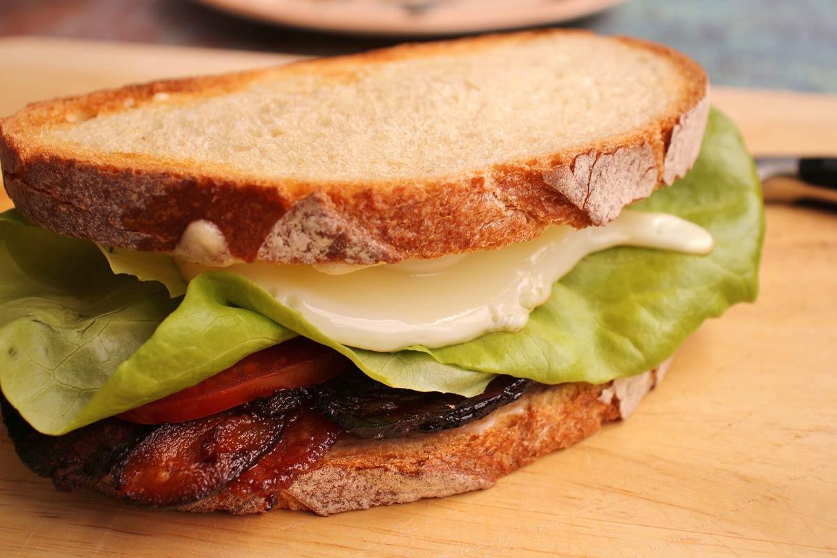 An assembled sandwich on a wooden board.