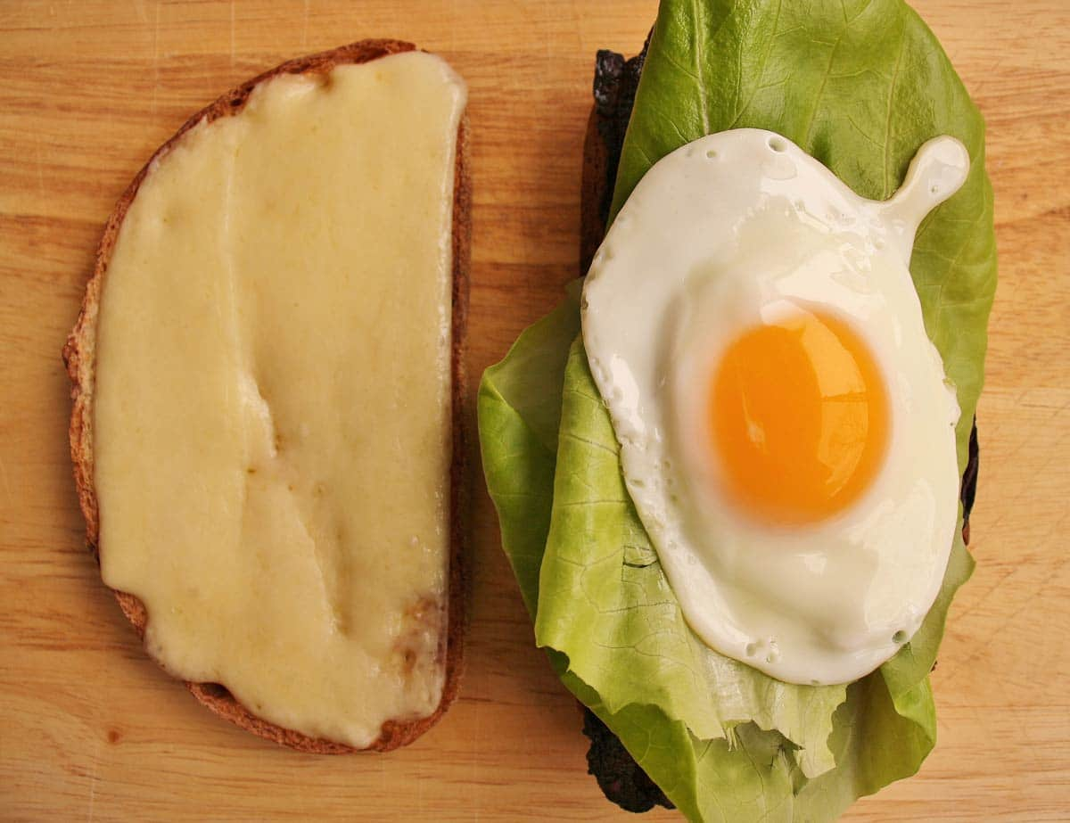 A partially assembled sandwich with a fried egg on top of lettuce.