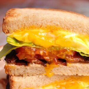 Closeup of Spanglish sandwich cross-section with runny egg yolk dripping down the front.