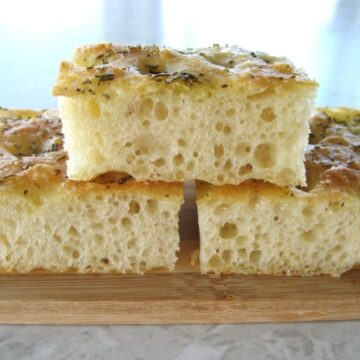 closeup side view of three squares of focaccia bread on a small wooden board