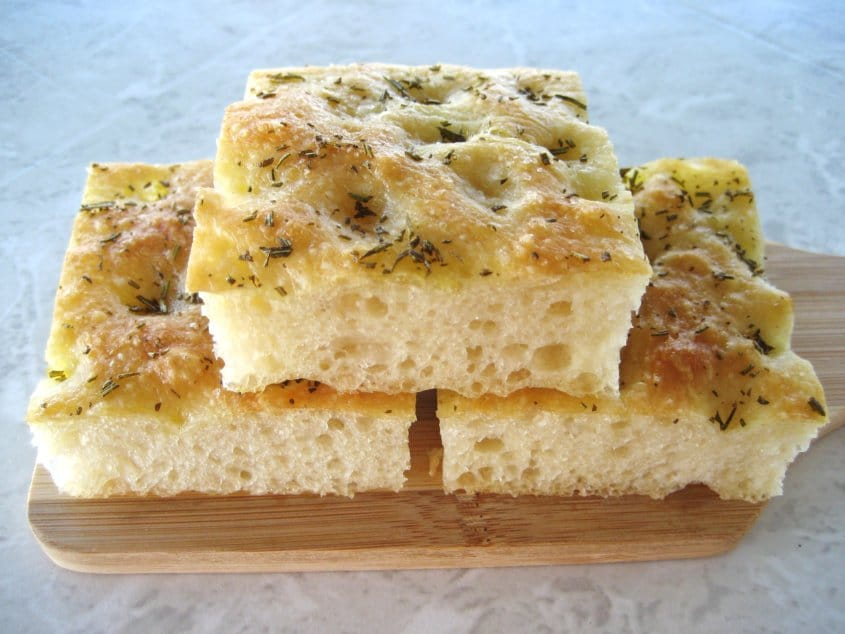 three squares of focaccia bread on a small wooden board