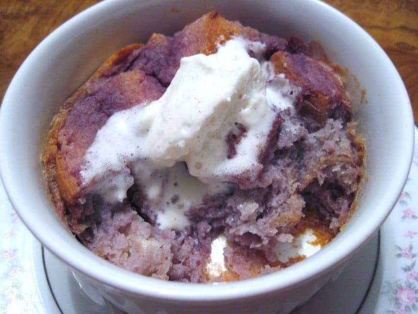 a half eaten dish of purple bread pudding with whipped cream on top