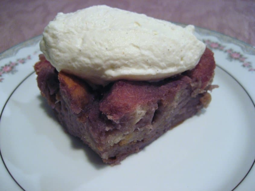 a square piece of purple bread pudding on a white plate topped with whipped cream