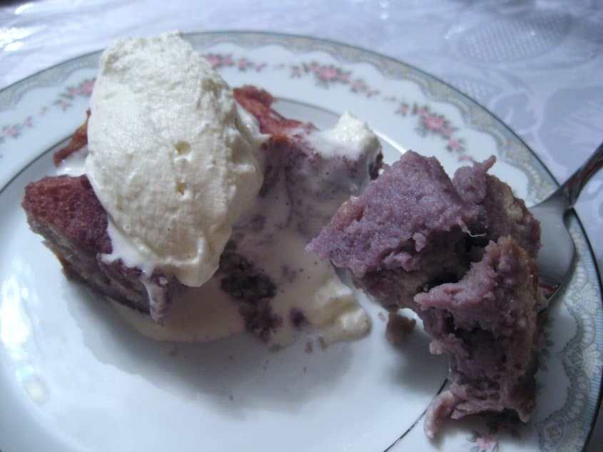 a plate of half eaten purple bread pudding with whipped cream on top