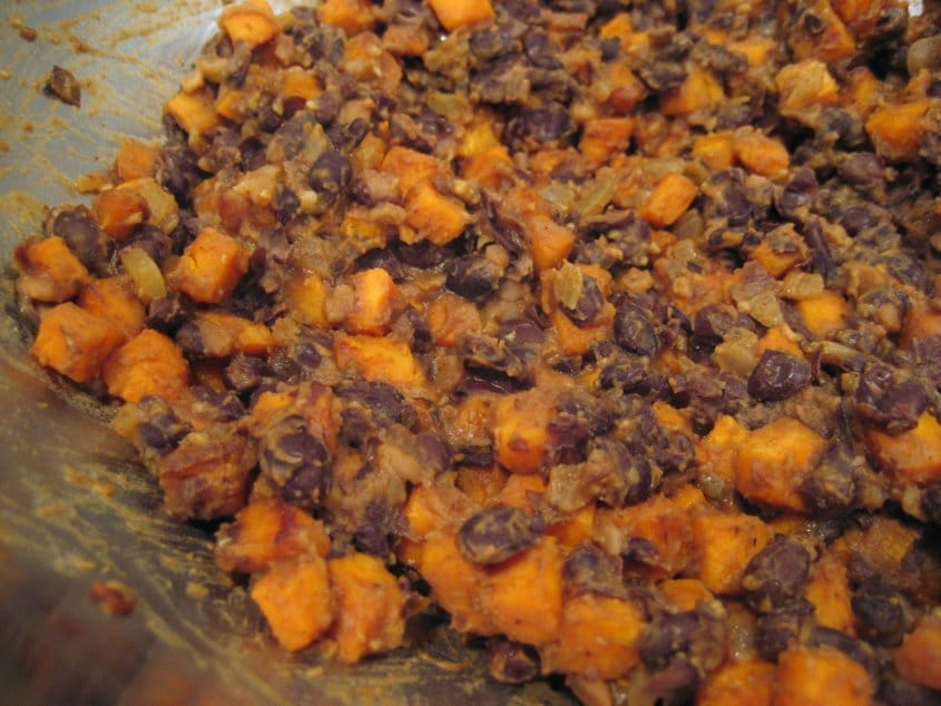 cooked black beans and cubed sweet potatoes in a metal mixing bowl