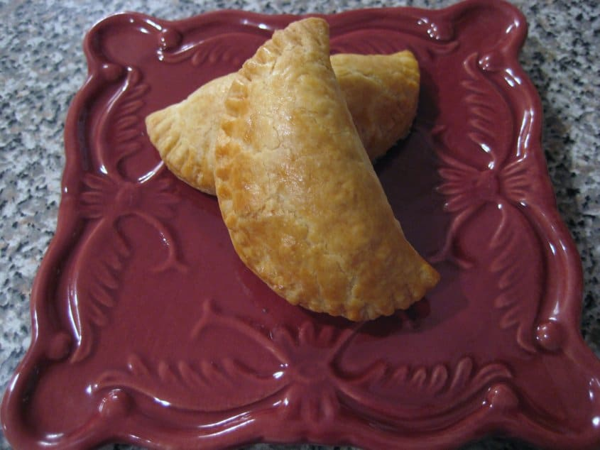 overhead view of two half moon shaped baked empanadas on a dark red square plate