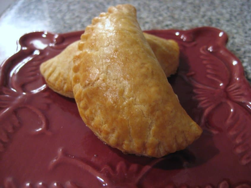 two half moon shaped empanadas on a dark red square plate