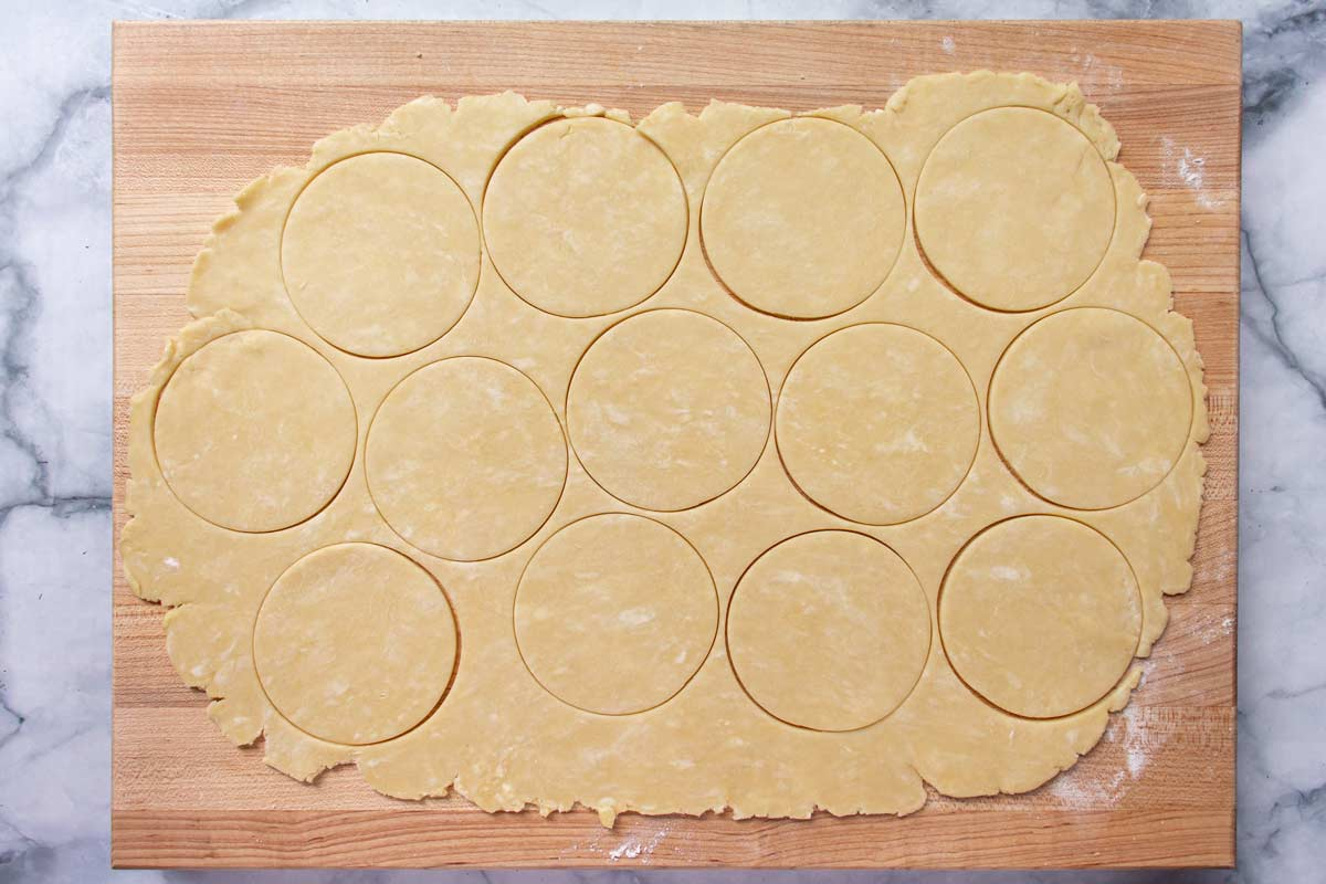 Rolled out dough on a wooden board cut into circles.