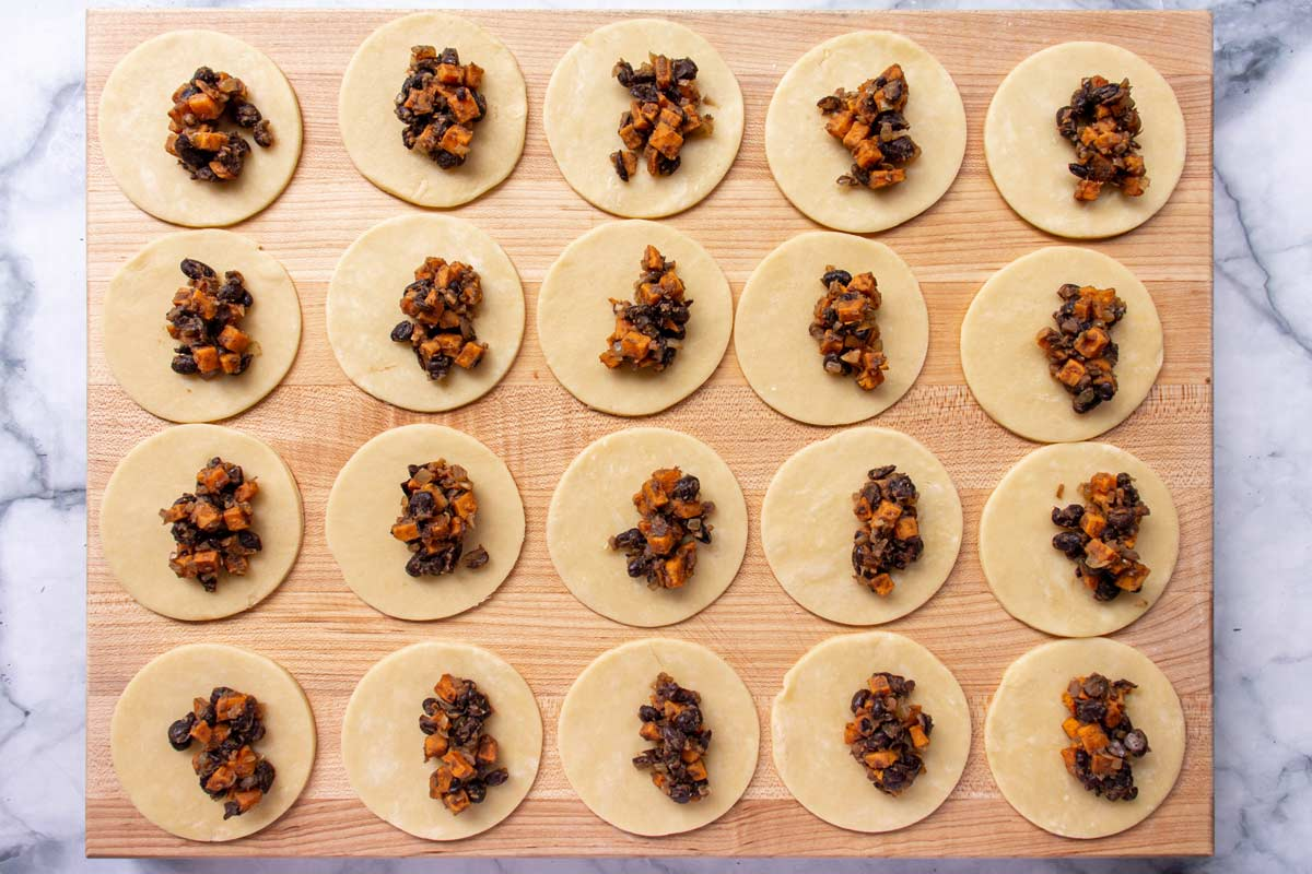 Circles of dough topped with sweet potato black bean filling on a wooden board.