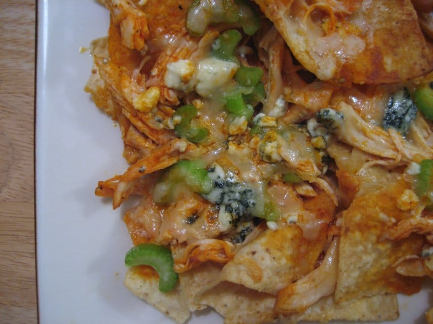 overhead closeup of Buffalo chicken nachos with chicken, blue cheese, and celery