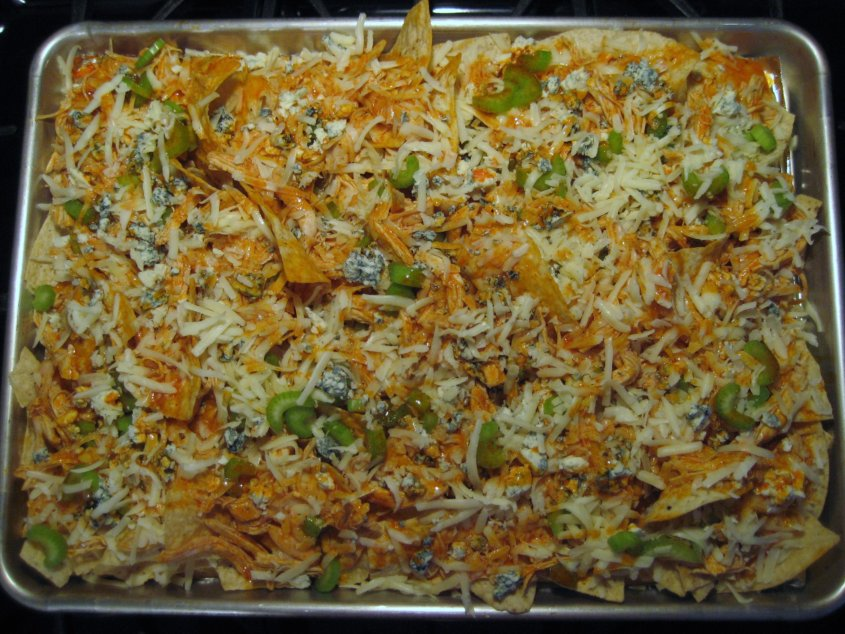 overhead view of a sheet pan of unbaked buffalo chicken nachos with shredded cheese on top