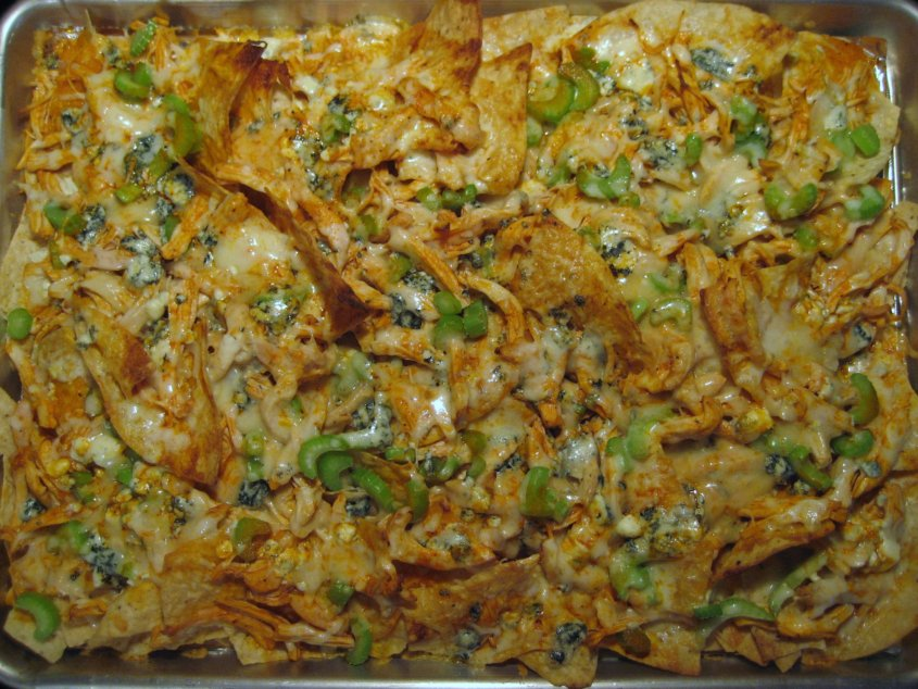 overhead view of a sheet pan of baked buffalo chicken  nachos with melted cheese on top